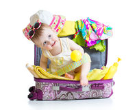 Baby girl sitting in suitcase with things for vacation travel Royalty Free Stock Images