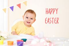 Baby girl sitting at the table and painting holiday easter eggs smiling happy childhood concept stock image