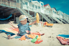 Baby girl sitting in te sand on the beach playing and laughing Stock Photos