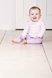 Baby Girl Sitting on Tiled Floor Royalty Free Stock Image