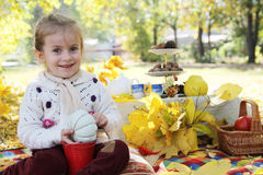 Baby girl sitting under autumn tree on picnic Stock Photography