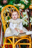 Baby girl sitting under christmas tree in room Stock Photo