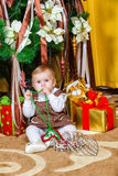 Baby girl sitting under christmas tree in room Royalty Free Stock Photography