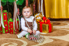 Baby girl sitting under christmas tree in room Royalty Free Stock Photos