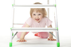 The baby girl is sitting under a stepladder Stock Image