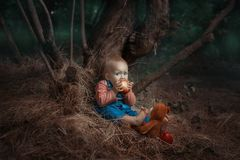 Baby girl eating an apple. Baby girl is sitting under a tree and eating an apple stock images
