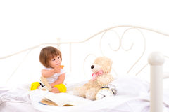 Baby girl sitting on white bed Stock Photography