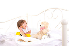 Baby girl sitting on white bed Stock Photos