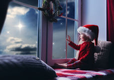 Baby girl sitting by the window. Merry Christmas and happy holidays! Cute little baby girl sitting by the window and looking at the christmas star. Room stock image
