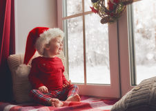 Baby girl sitting by the window Royalty Free Stock Image