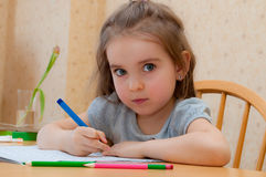 Baby girl sitting writing at the table. Baby girl sits and learns to write at the table royalty free stock photo