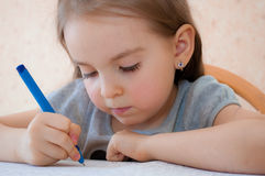 Baby girl sitting writing at the table. Baby girl sits and learns to write at the table stock image