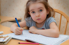 Baby girl sitting writing at the table. Baby girl sits and learns to write at the table stock photo