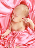 Baby girl sleeping. A newborn baby girl sleeping in pink sheets royalty free stock photography