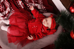 Baby girl sleeping in baby bed on Christmas background. Studio photo of cute beautiful baby girl sleeping in baby bed on Christmas background Stock Photography