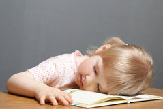 Baby girl is sleeping on the book Stock Images