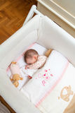 Baby girl sleeping in a cot with pacifier and toy Royalty Free Stock Photos