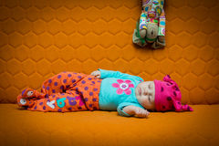 Baby girl sleeping on a couch. Baby girl sleeping on an orange couch. Bright colors, dots, honey comb Stock Images