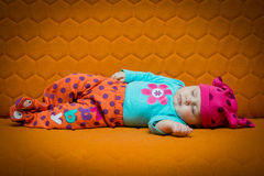 Baby girl sleeping on a couch. Baby girl sleeping on an orange couch. Bright colors, dots, honey comb Stock Photos