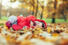 Baby girl sleeping in fallen leaves Royalty Free Stock Image