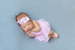 Baby girl sleeping on her tummy. Sweet baby girl sleeping on her tummy, wearing pink little dress, in a flowery hairband Royalty Free Stock Photo
