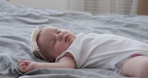 Baby girl sleeping at home. Tired baby girl sleeping on bed at home stock video footage