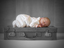 Baby girl sleeping. Newborn sleeps peacefully on an old suitcase Royalty Free Stock Images