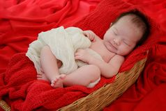 baby girl is sleeping on red fabric blanket royalty free stock photography