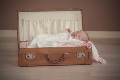 Baby girl sleeping. Baby girl sleeps peacefully in old suitcase with her pink blanket Stock Images