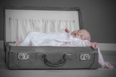 Baby girl sleeping. Baby girl sleeps peacefully in old suitcase with her pink blanket Royalty Free Stock Images