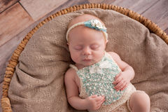 Baby Girl Sleeping in a Wicker Basket Stock Photo