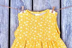 Baby girl sleeveless yellow top. Infant baby-girl cotton dress drying on rope on old wooden background. Kids clothing in laundry Royalty Free Stock Image