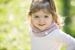 Baby girl with smile on adorable face on sunny day royalty free stock image