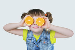Baby girl with a smile and an orange in the hands Royalty Free Stock Photo