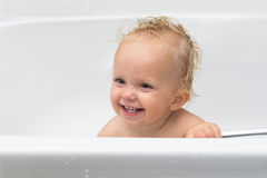 Baby girl smiles in the bathroom. Adorable baby girl having bath in a white bathtub, smiling and looking at parent Stock Images