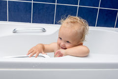 Baby girl smiles in the bathroom. Adorable baby girl having bath in a white bathtub, smiling and looking at parent. Blue tiles behind Stock Photos