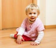 Baby girl smiling on floor Stock Photo