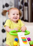 Baby girl smiling while standing in a walker Royalty Free Stock Images