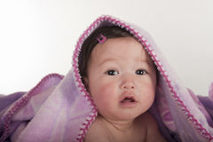 Baby girl smiling from underneath blanket Royalty Free Stock Images