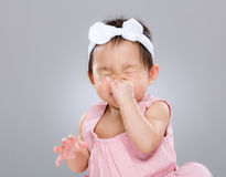 Baby girl sneeze. With gray background Royalty Free Stock Image