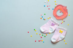 Baby girl socks and teether toy. Baby girl accessories concept: socks and teether toy, over grey background with copy space; top view, flat lay stock photo