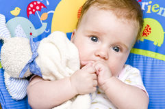 Baby girl with soft toy. A cute baby girl cuddling her soft toy stock photography