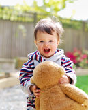 Baby girl with soft toy in her hands in the garden Stock Images