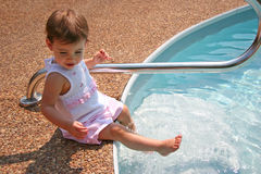 Baby Girl Splashing. Beautiful baby girl splashing water in pool with feet. Shot with Canon 20D stock photo