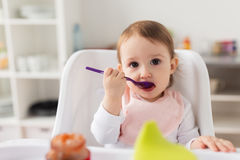 Baby girl with spoon eating puree from jar at home Royalty Free Stock Photography