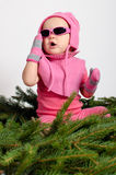 Baby Girl on Spruce Needles. Baby girl in pink dress is sitting on lovely green spruce needles Stock Image