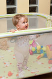 Baby girl stand in playpen. Cute baby girl stand in playpen, smile on her face Royalty Free Stock Photography