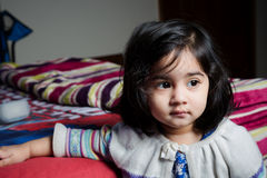 Baby girl standing with bed. Royalty Free Stock Image
