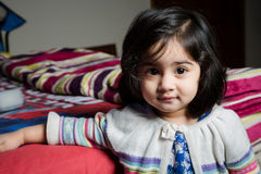 Baby girl standing with bed. Stock Photo