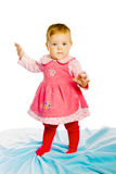 Baby girl standing on a blue blanket. Studio photo Royalty Free Stock Photos
